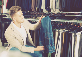 Man choosing on new trousers