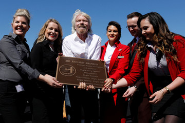 Branson holds a bronze plaque as he is surrounded by Virgin Air employees after he was inducted into the Flight Path Walk of Fame in Los Angeles