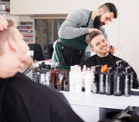 Glad guy creating shape for beard of client