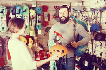 Young family couple buying alpinism equipment