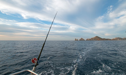 Fishing rod on charter fishing boat on the Sea of Cortes / Gulf of California viewing Lands End at Cabo San Lucas Baja Mexico BCS