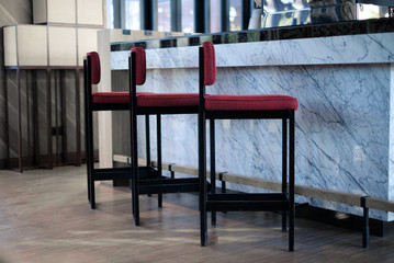 Row of empty wooden chairs in front of marble counter bar