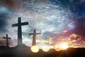 Concept conceptual black cross religion symbol silhouette in grass over sunset or sunrise sky