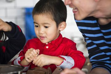 お菓子づくりを手伝う男の子。