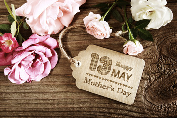 Mothers Day message with small pink roses on wooden table