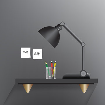 Black lamp turn off on a black working table with a three pencils such as green,red,yellow in a mini stainless cylinder and white sticky notes as write a message that 9am. and 2pm. stick on a grey wal