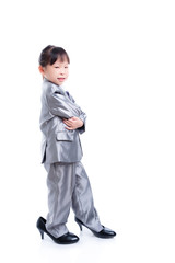 Little asian girl wearing suit and big high heel shoes standing over white background