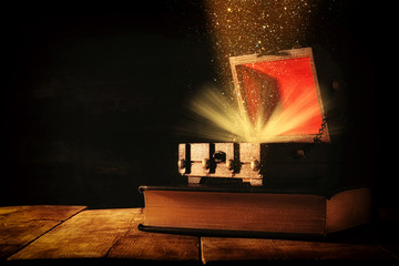 Image of mysterious treasure chest with glitter light and smoke over old book on wooden table.