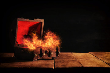 Image of mysterious treasure chest with flames over wooden old table.