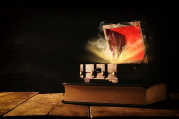 Image of mysterious treasure chest with light and smoke over old book on wooden table.