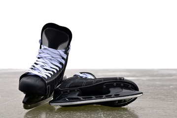 Black hockey skates on a ice rink with copy space.