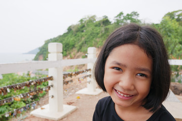 Portrait of a little girl with a smile on a natural background