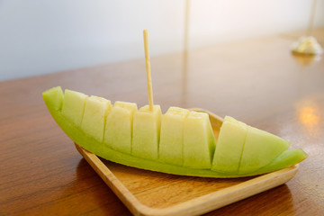 Fresh sweet green melon on wooden dish, selective focus.