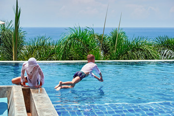 Children play in pool in clothes for protection from ultraviolet rays. Dive into water. Outdoor pool on background  palm and sea.