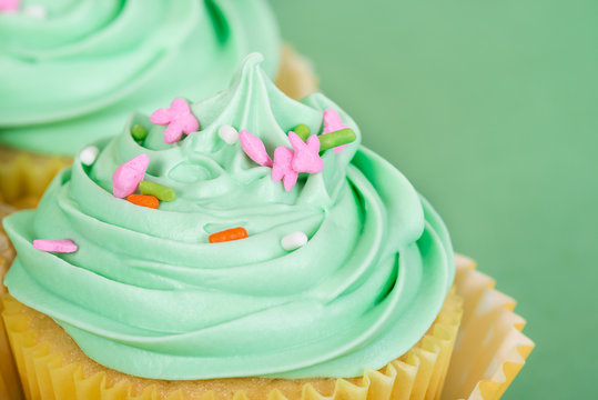Close-up of Easter spring cupcake with sprinkles. Green background with copy space.