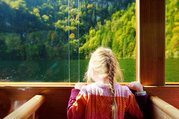 Fototapete - Little girl enjoying a view of deep green waters of Konigssee while traveling by electric boat. Konigsee is known as Germany's deepest and cleanest lake, located in Bavaria.