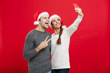 Christmas Concept - Young attractive couple taking a selfie by mobile phone celebrating in Christmas day