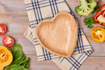 Include fresh organic vegetables and wood heart disk on wooden floor with copy space still life