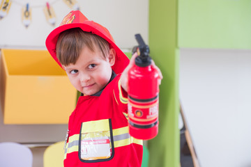 Caucasian boy kid dress up to fireman and use speaker at roll play classroom,Kindergarten preschool education concept