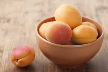 Apricots in a clay bowl on a wooden table
