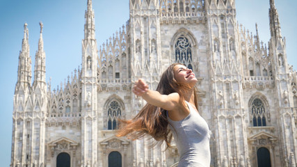 Beautiful young tourist girl (woman) in Milan, feels free, happy smiling, the backdrop of the Milan cathedral. Concept: tourism, love to travel, communication, freedom, love life, a big city.