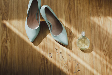 Leather tiffany color high heels wedding shoes on the wooden background in sun rays. Fashion jewellery earrings and bracelet with perfumes. Very elegant light blue bridal pumps.