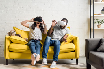 frightened african american couple in virtual reality headsets sitting on couch Wall mural