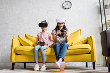 young mother and daughter in vr headsets playing video games at home on couch