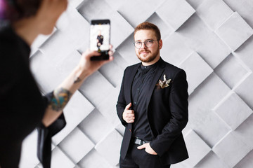 Woman making photo of groom on phone in gray studio background isolated