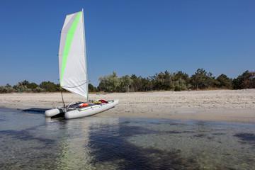 sailing catamaran on a deserted beach