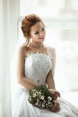 Beautiful model wearing white wedding dress is posing in an interior studio