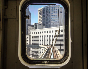Morning Commute In The City. View through tram window of the city skyline and train tracks Detroit, Michigan.