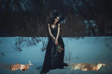 Beautiful model wearing black dress is posing on a snow