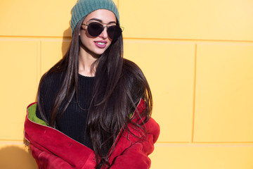Outdoor fashion portrait of glamour sensual young stylish lady wearing trendy fall outfit , red leather coat,trendy hat , and stylish sunglasses.Looking to the side.Copy space.
