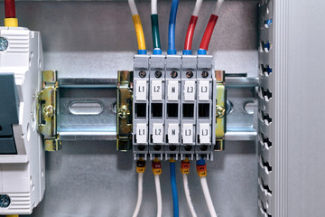 Multiple connection terminals in the electrical Cabinet. Wires are connected to the terminals. On wires and terminals marking color and digital. Modular circuit breaker and perforated cable channel.