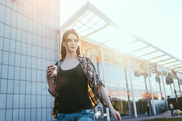 hipster girl drinks coffee near shopping center