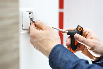 Montaż włącznika światła.  Elektryk montuje włącznik światła w instalacji elektrycznej.