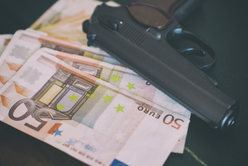 Lot of euro banknotes and gun on the table.