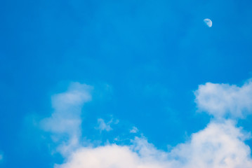 Bright blue sky with moon and clouds,