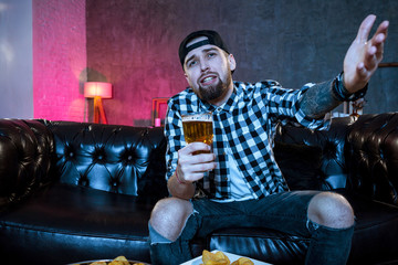 Young fanatic man watching football game on television nervous a