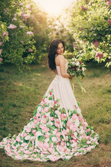 young woman in a peony dress stands in a blooming lilac garden at sunset