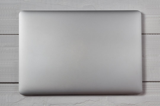 White laptop on wooden table