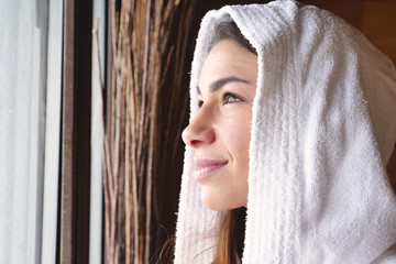 A beautiful woman looks out the window wearing a white bathrobe and drinks hot tea or herbal tea looking out. The woman relaxes and thinks as she looks out.