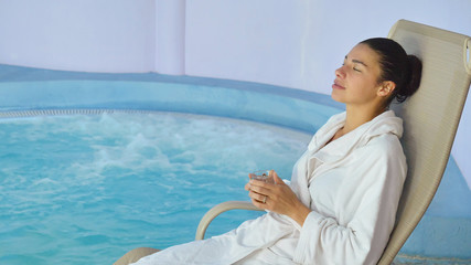 Beautiful young girl (woman) relaxed in a spa, in a white bathrobe, on a blue background. Concept: spa procedures, body massages, spa cream, relax, spa water treatments, swimming pool