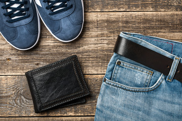 Blue Jeans with belt, shoes and leather wallet on wooden background