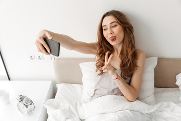 Portrait of amusing woman resting in bed after sleep with white clean linen at bedroom, and taking selfie on cell phone showing victory sign