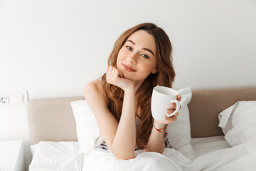 Portrait of young caucasian woman resting after sleep in cozy bed in hotel, and drinking morning coffee or tea