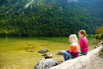 Fototapete - Two cute sisters enjoying the view of deep green waters of Konigssee, known as Germany's deepest and cleanest lake, located in the extreme southeast Berchtesgadener Land, Germany