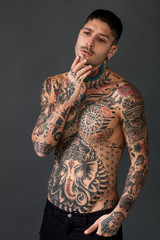Handsome and pensive bare-chested tattooed man portrait