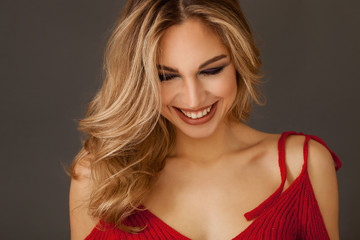 Gorgeous blonde woman portrait wearing red dress and smiling widely